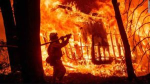 Firefighter sprays water on flames in California. Image Credits: CNN